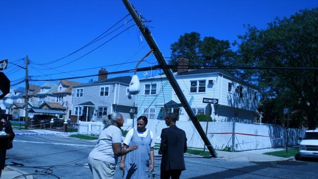 Neighbors traded stories as a utility pole leans in the background.